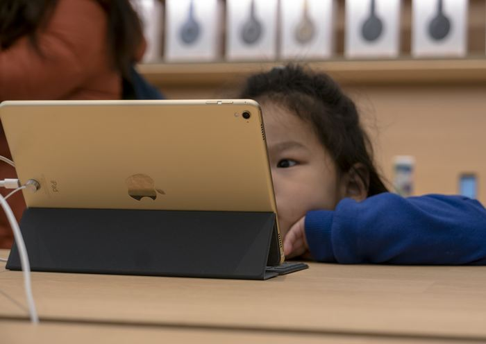 NANJING, JIANGSU PROVINCE, CHINA - 2017/03/25: A kid is watching video on iPad in the apple shop. On the March 25, Apple opened 3 new retail shop in the world, one of them is located in Nanjing Jinmao Plaza, which is the third Apple shop in Nanjing city. (Photo by Zhang Peng/LightRocket via Getty Images)