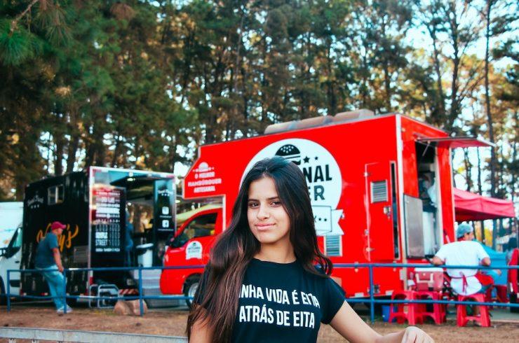 jeune femme devant un rassemblement de footdtrucks, source alternative de revenu dans le sport business