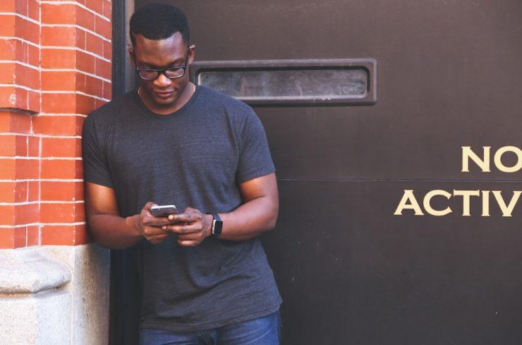 jeune homme consultant son smartphone dans le rue, sa data étant analysée par des spécialistes du sport business