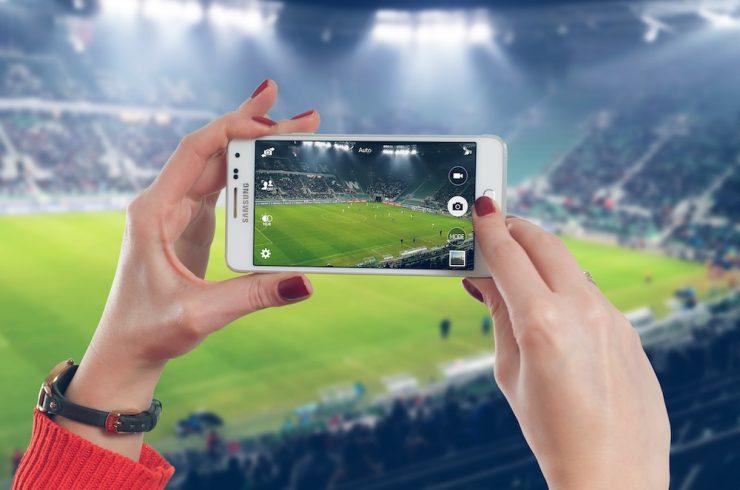 smartphone tenue par une femme prenant la photo d'un stade de football, explicitant la fidélisation dans le sport business